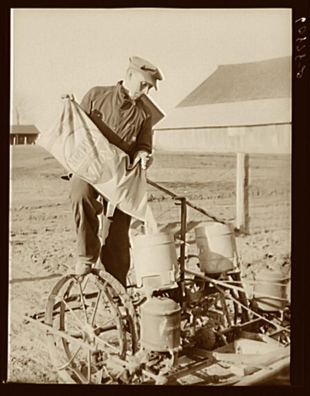 A farmer in Iowa pours fertilizer into a corn planter in 1940. (Credit: Library of Congress/John Vachon)
